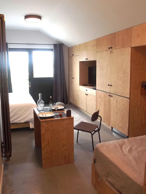 Vue d'une de nos suites du rez de chaussée à louer avec lit double, espace repas et accès à une terrasse privée.