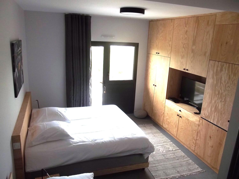 Exemple d'une suite à louer sur Plouharnel avec le lit double, la TV et l'accès à la terrasse privée.