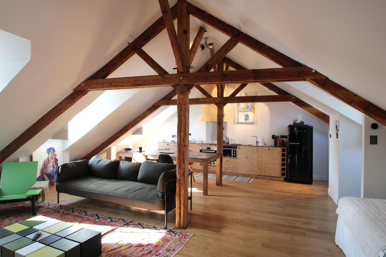 Location d'appartement à Vannes, salon avec canapé et cuisine toute équipée.