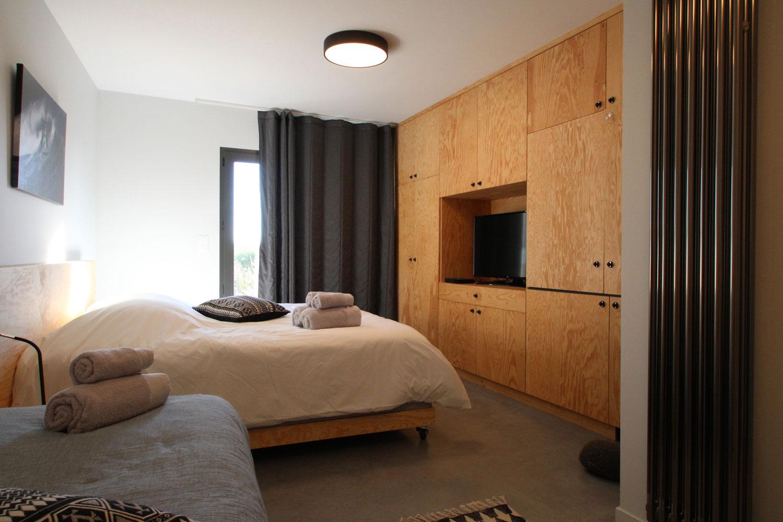 Exemple d'une de nos suites à louer avec vue sur le lit double, la banquette d'appoint et la TV.