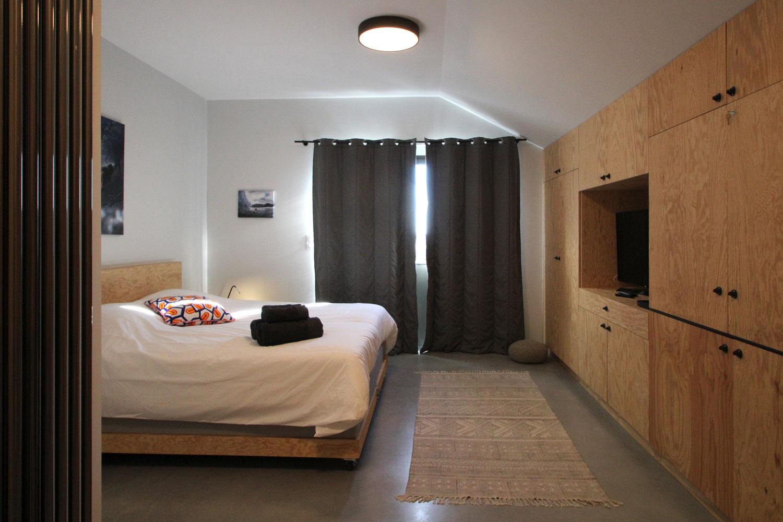 Exemple d'une de nos suite en location avec vue sur le lit double et la TV.
