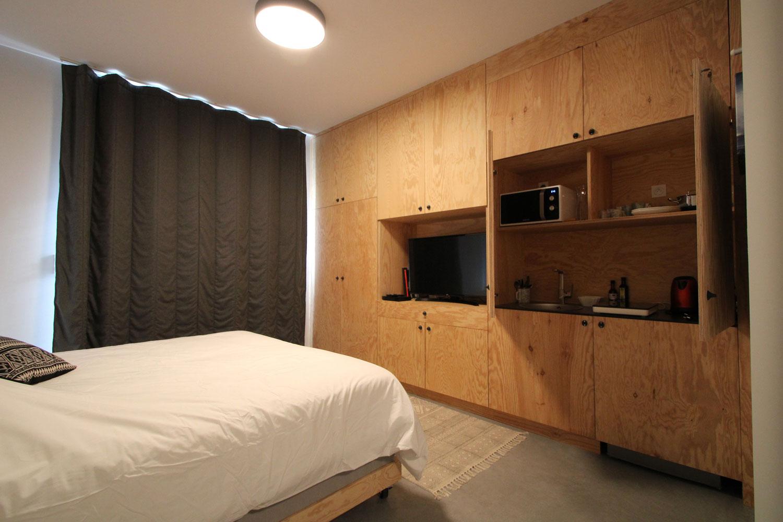 Exemple d'une suite dans notre location avec vue sur le lit double, les équipements, la kitchenette et l'écran plat.