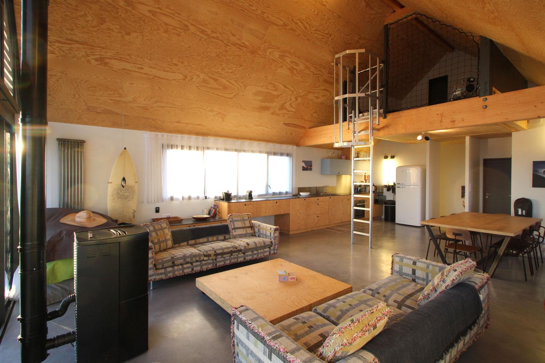 Vue du salon avec canapés, poêle et cuisine équipée de notre location de maison à Plouharnel.