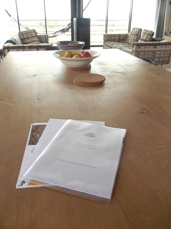 Grande table à manger et guide d'accueil de notre location de Sainte-Barbe.