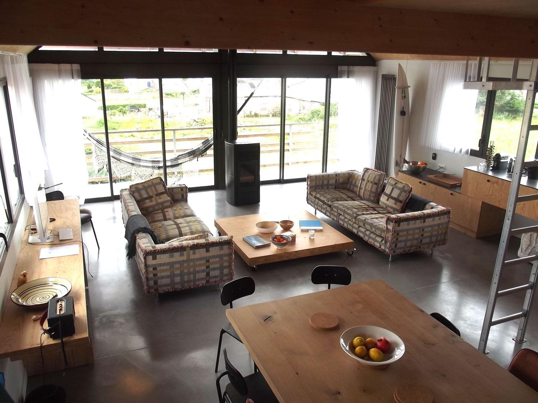 Salon canapés, poele et grande table à manger, à l'étage de notre location de maison à Plouharnel.